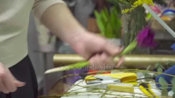 Florist is making bouquet with violet tulips