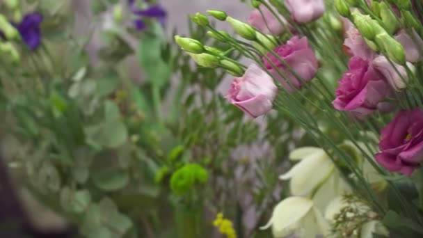 Florist is making bouquet with violet tulips closeup