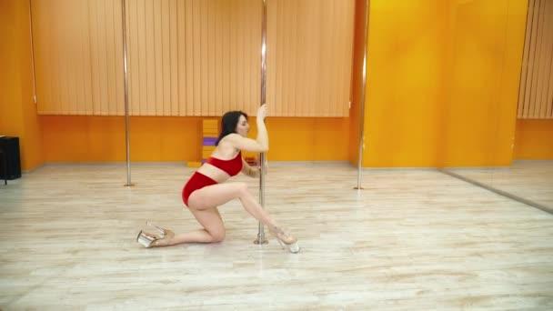 Vonzó fiatal nő táncol egzotikus tánc közelében a pole pole tánc stúdió