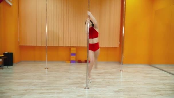 Brünette Frau exotischen Tanz in der Nähe der Pole im Tanz studio