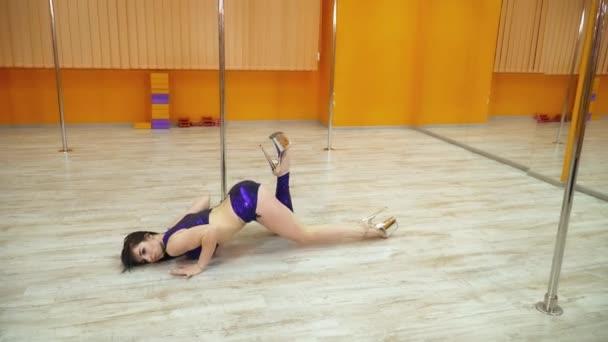 Brunette woman dancing near the pole in the dancing studio