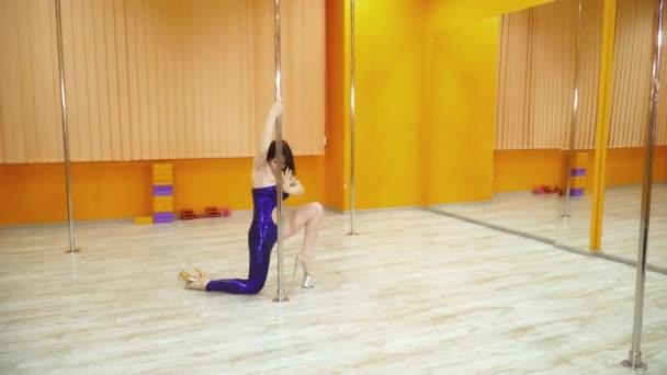 Beautiful brunette woman dancing near the pole in strip shoes