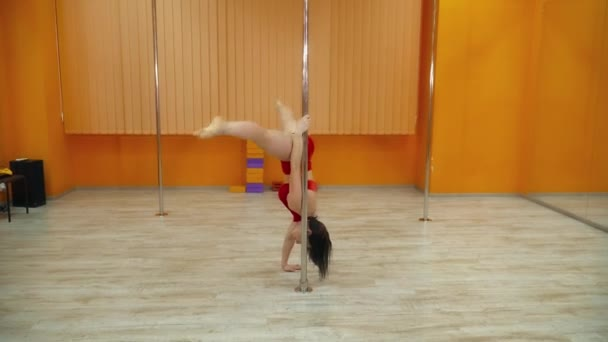 Beautiful brunette woman making tricks on the pole in the dancing studio