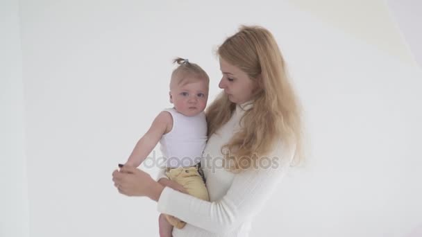 Young mother holding her crying small baby son on hands, slow motion