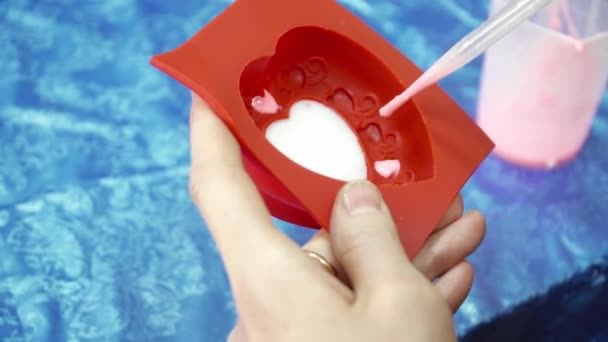 Womans hands adding soap base to the heart template with dropper