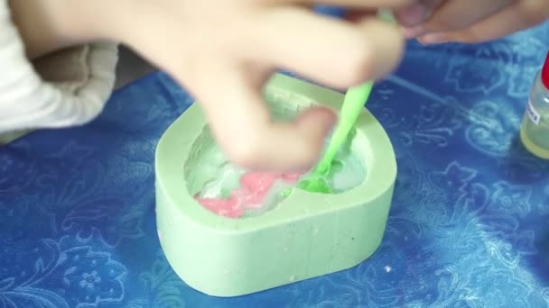 Womans hands pouring soap base to the template with dropper for handmade soap creation