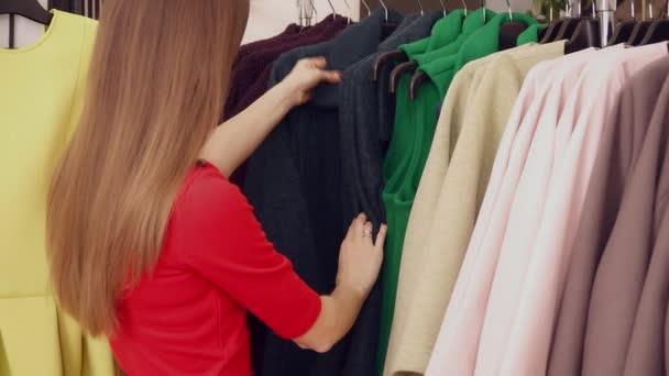 Žena v červených šatech při volbě kabát v detailním boutique