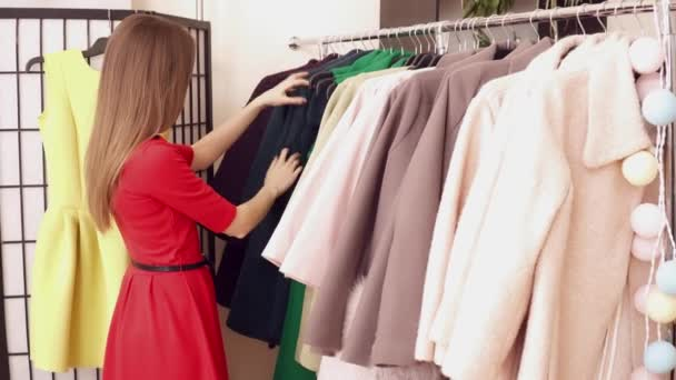 Žena v červených šatech při volbě kabát v butiku