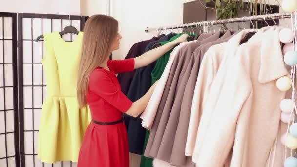 mladá žena vybírá oblečení v obchodě