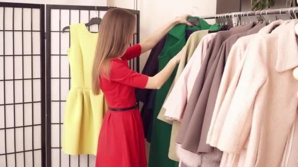 Bruneta žena výběru oblečení v butiku