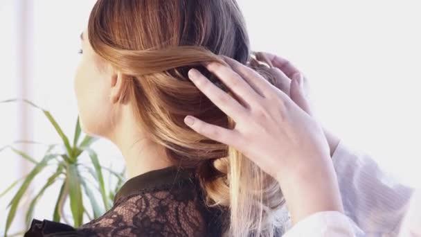 Creazione di un taglio di capelli per una bella donna nel salone di capelli del parrucchiere