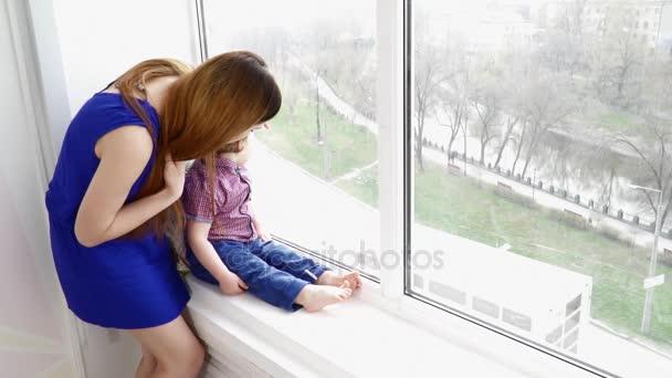 Mladá krásná matka s její dítě chlapec syn Zpomalený pohyb při pohledu do okna