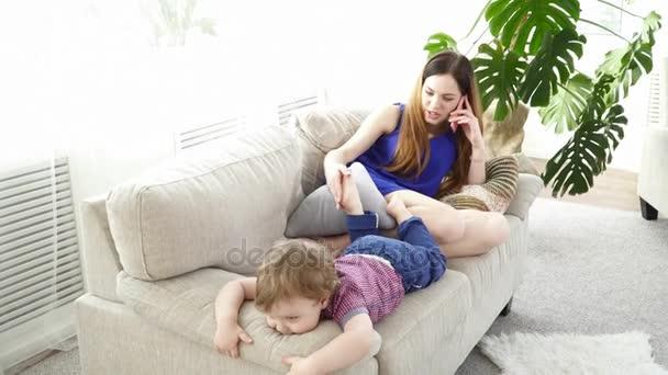 Malý chlapeček, který je baví, zatímco jeho matka mluví o telefonu