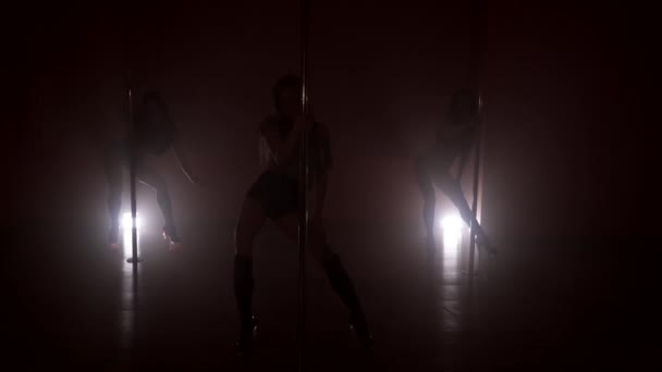 Silhouette Of Three Slim Women Dancing Near The Poles In Smoke