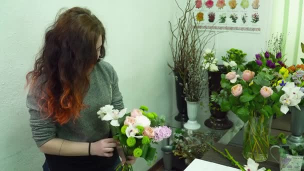 Florist making a beautiful bouquet with the orchids