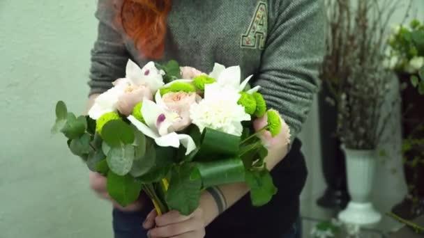 Floristin macht einen schönen Strauß mit Orchideen und Rosen