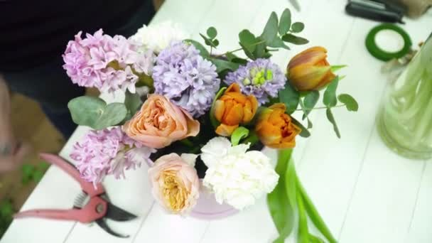 Florist creating a beautiful bouquet in the box on the table