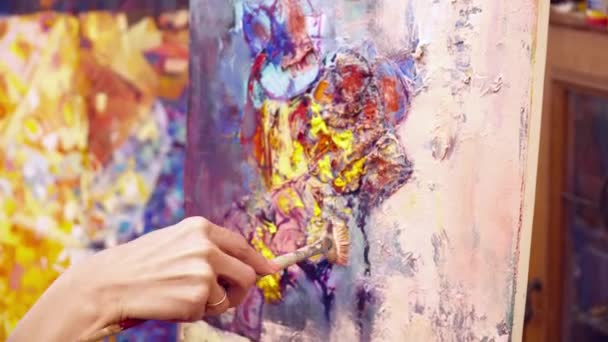 Woman artist paining picture on the canvas with the brush closeup