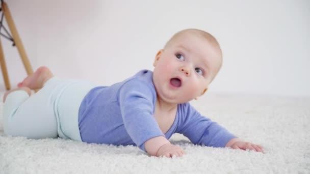 hübscher kleiner Junge von 6 Monaten auf dem Teppich liegend Nahaufnahme