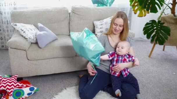 Mladá matka hraje s její syn 6 měsíců starý s balóny