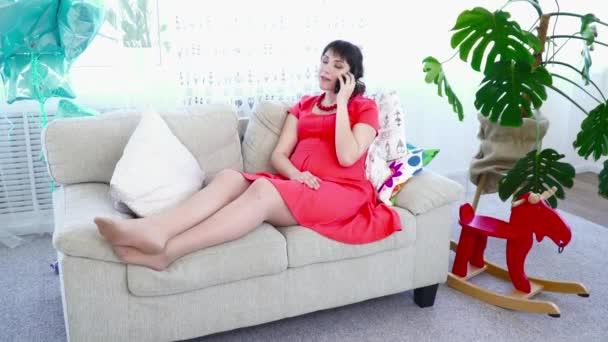 Těhotná žena mluví po telefonu