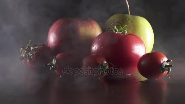Čerstvé chutné ovoce a zeleniny v kouři na černém pozadí