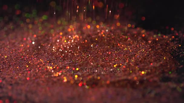 Red fashion sparkles falling on the black background, abstract slow motion