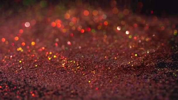Red shiny fashion sparkles falling on the black background, abstract slow motion