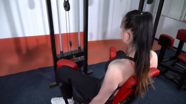 Young woman with a ponytail training on the abduction machine in gym