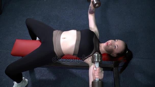 Mladá žena cvičení s barbells