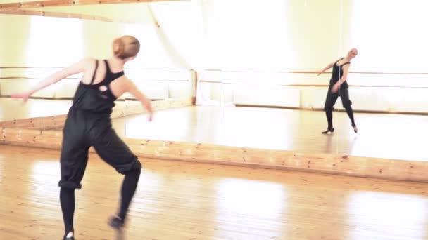 Mladá bruneta žena provádějící lidový tanec před zrcadlem
