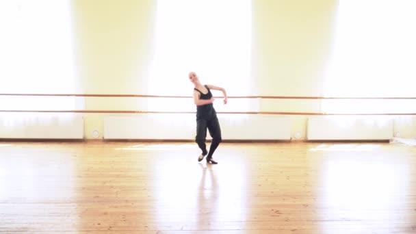 Mladá žena provádějící lidový tanec ve velké taneční studio