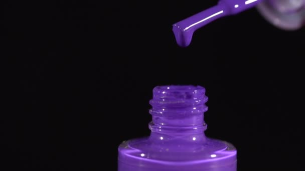 Closeup von violettem Nagellack drapiert in die Flasche Zeitlupe