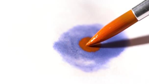 Closeup štětečkem s modrými a oranžovými akvarel zpomalené
