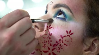 Makeup artist making face art with a stencil with red flowers for a woman closeup