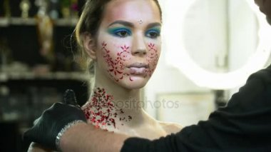 Makeup artist covering womans body with the sparkles,body art closeu