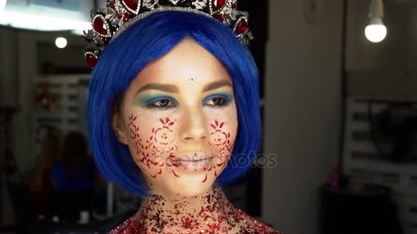 Portrét krásné mladé ženy v umění tvář s korunou při pohledu do kamery, pomalý pohyb