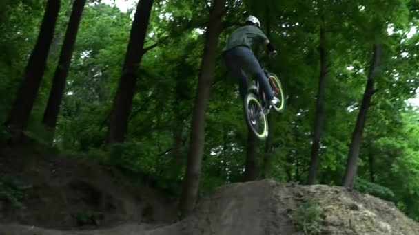 Man in the helmet jumping on bike in the forest slow motion