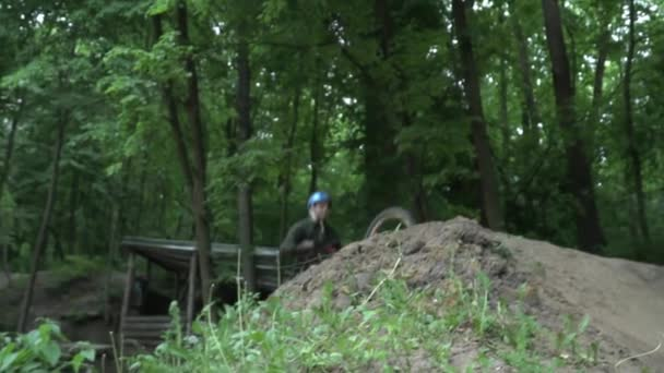 Young man in the helmet jumping on modern bike in the forest slow motion