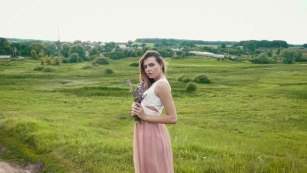 Mladá krásná mladá žena na louce s divokými květy v dlaních