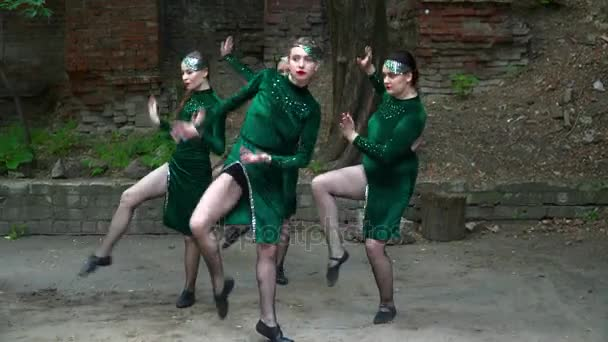 Group of young women in green costumes dancing on the street