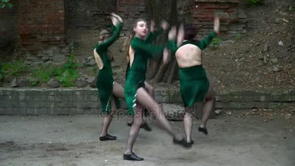 Gruppe junger Frauen tanzt auf der Straße neben dem Baum