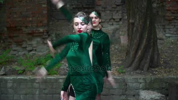 Gruppe von Frauen in grünen Kostümen tanzt in der Nähe des Baumes Nahaufnahme