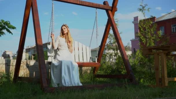 Krásná žena v bílých šatech kyvné