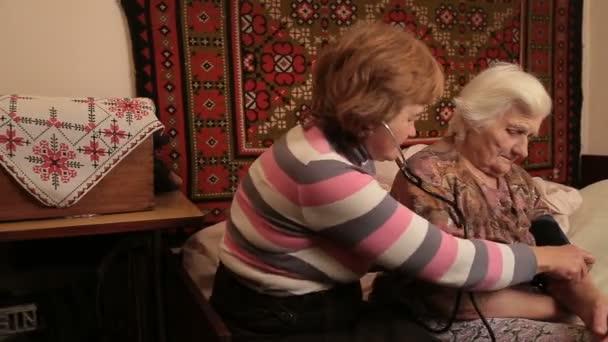 Frau misst den Puls von Senioren