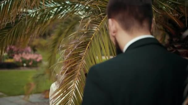 Young couple in love with newlywed fool around with palm leaves.