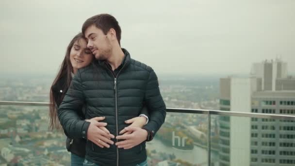 Couple of young people embrace on roof of tall house in city of megapolis.