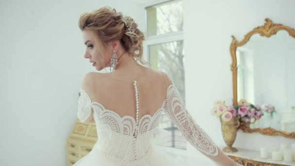 Mladá blondýnka nevěsta v bílých svatebních šatech pózuje před kamerou, otáčí