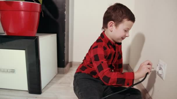 A cute guy in red and black plaid shirt shoves an electric plug into an outlet
