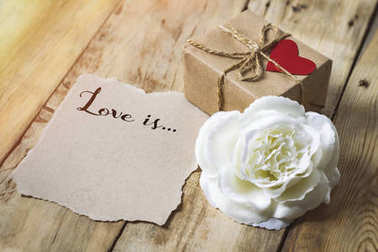 Inscription on a piece of paper Love is ... Gift box with a hear